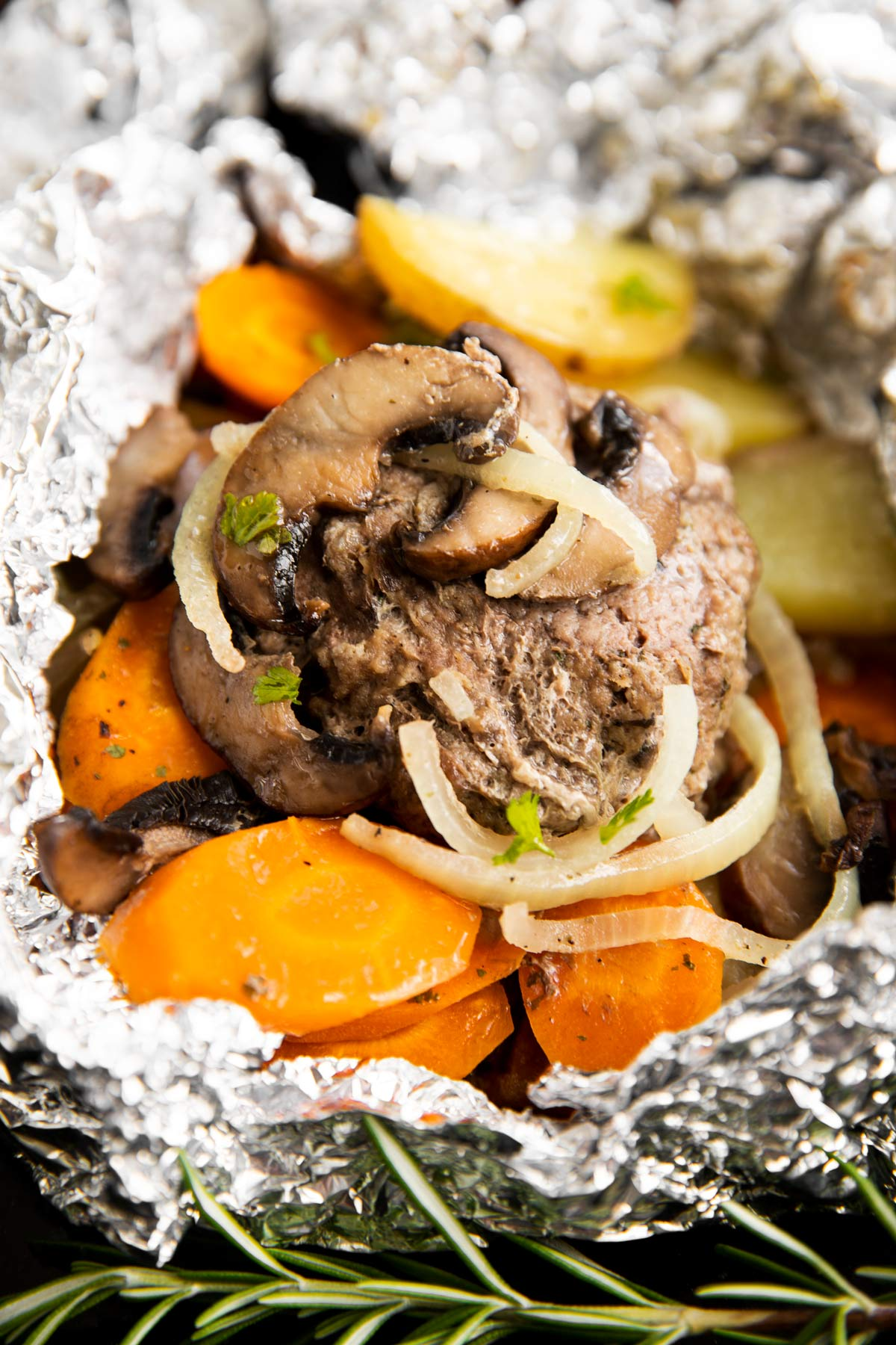 frontal close up of hamburger patty with carrots and potatoes in foil