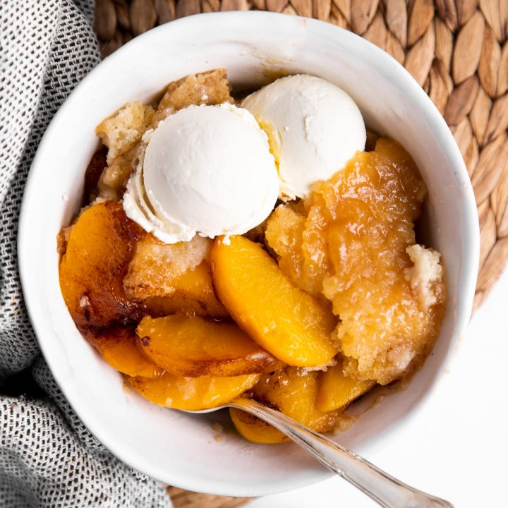 overhead view of a bowl with peach cobbler