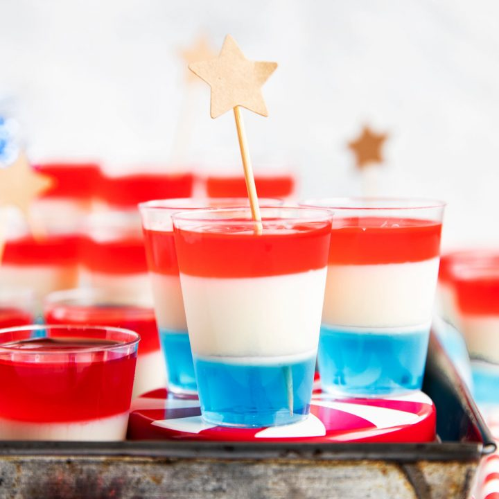 several plastic shot glasses with layered jello and star decor