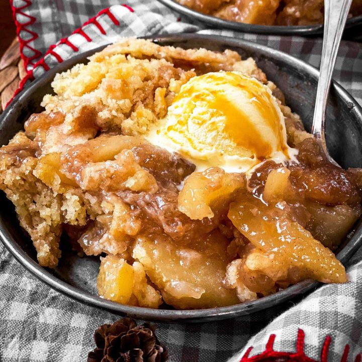 apple dump cake with ice cream in old metal plate