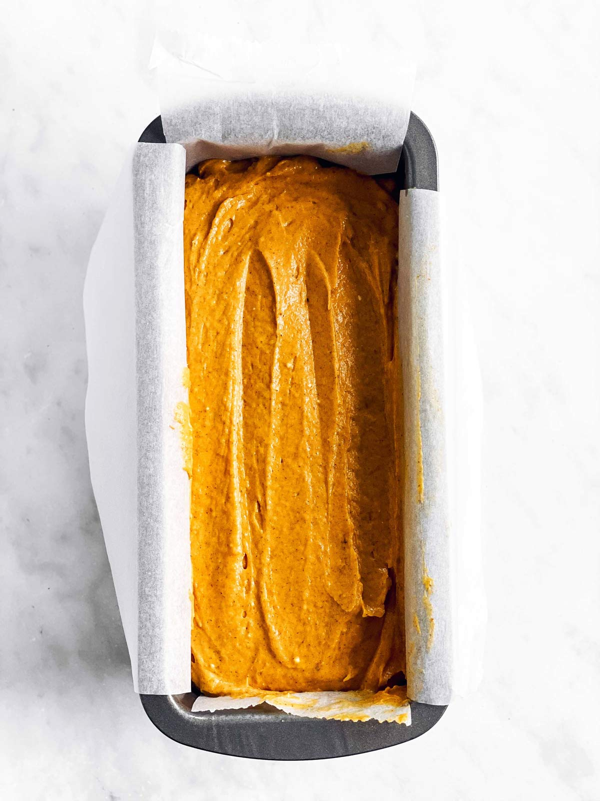 loaf pan with batter for pumpkin bread