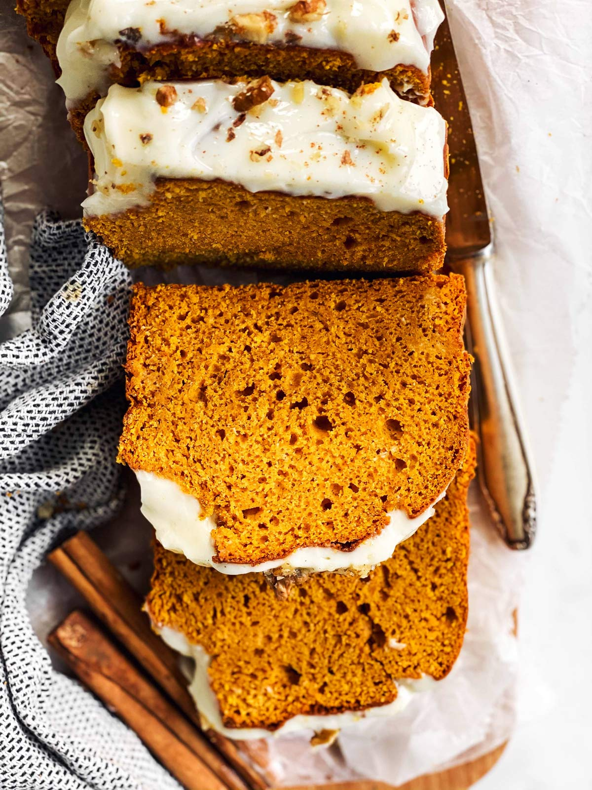 sliced pumpkin bread on chopping board with frosting