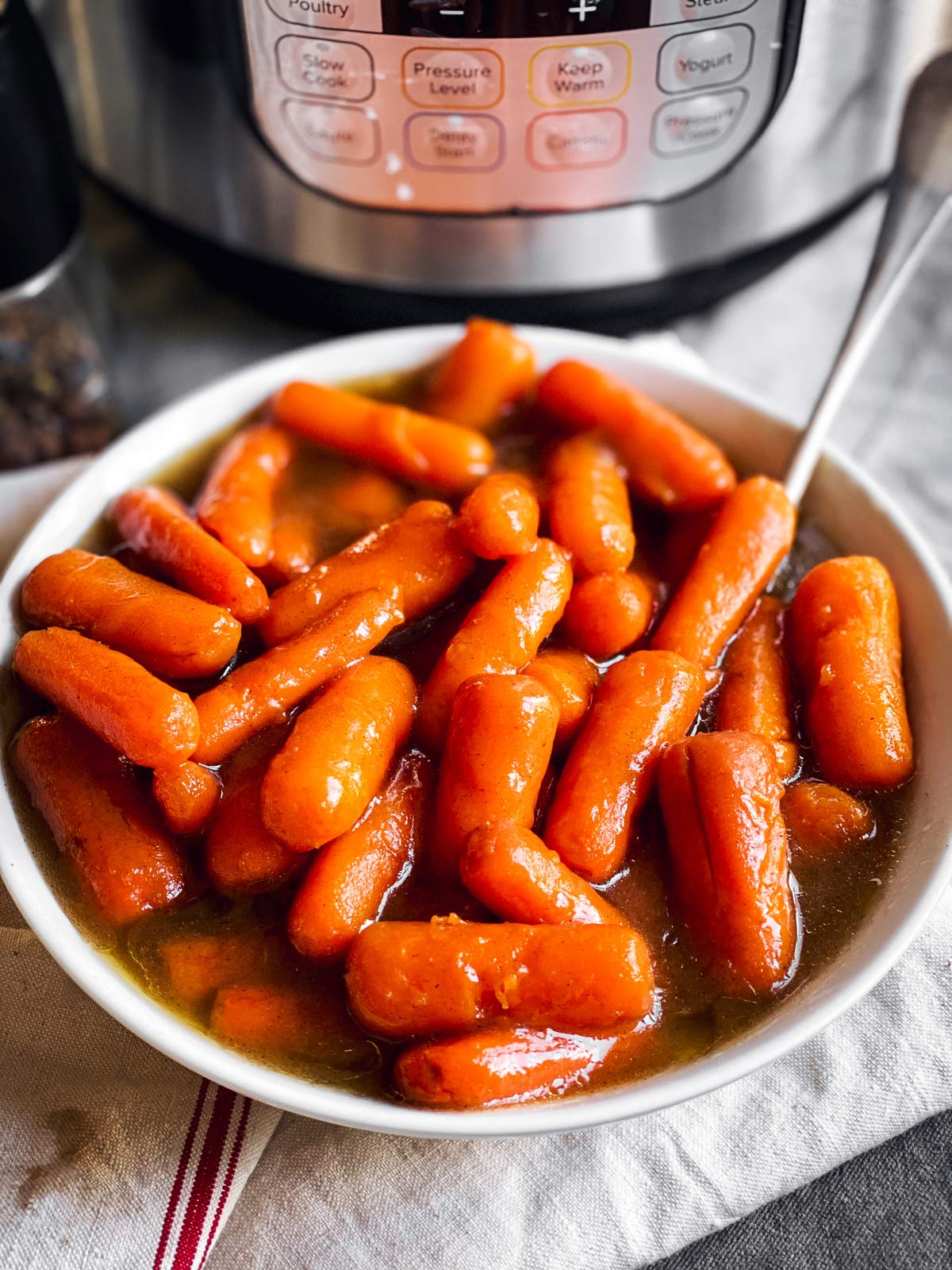 bowl with glazed carrots in front of instant pot