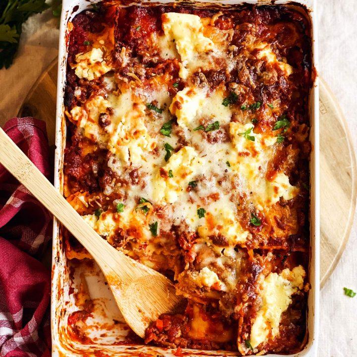 white casserole dish with ravioli lasagna on tablecloth