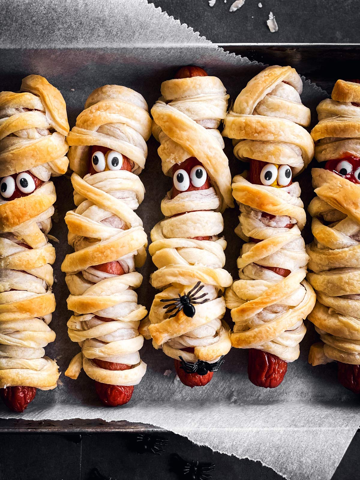 close up of mummy decorated hot dogs on lined baking sheet