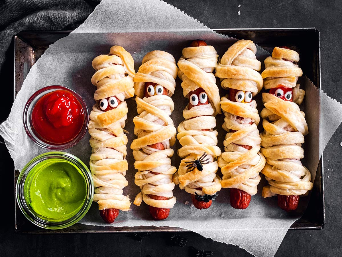 overhead view of small metal pan with mummy hot dogs on dark background