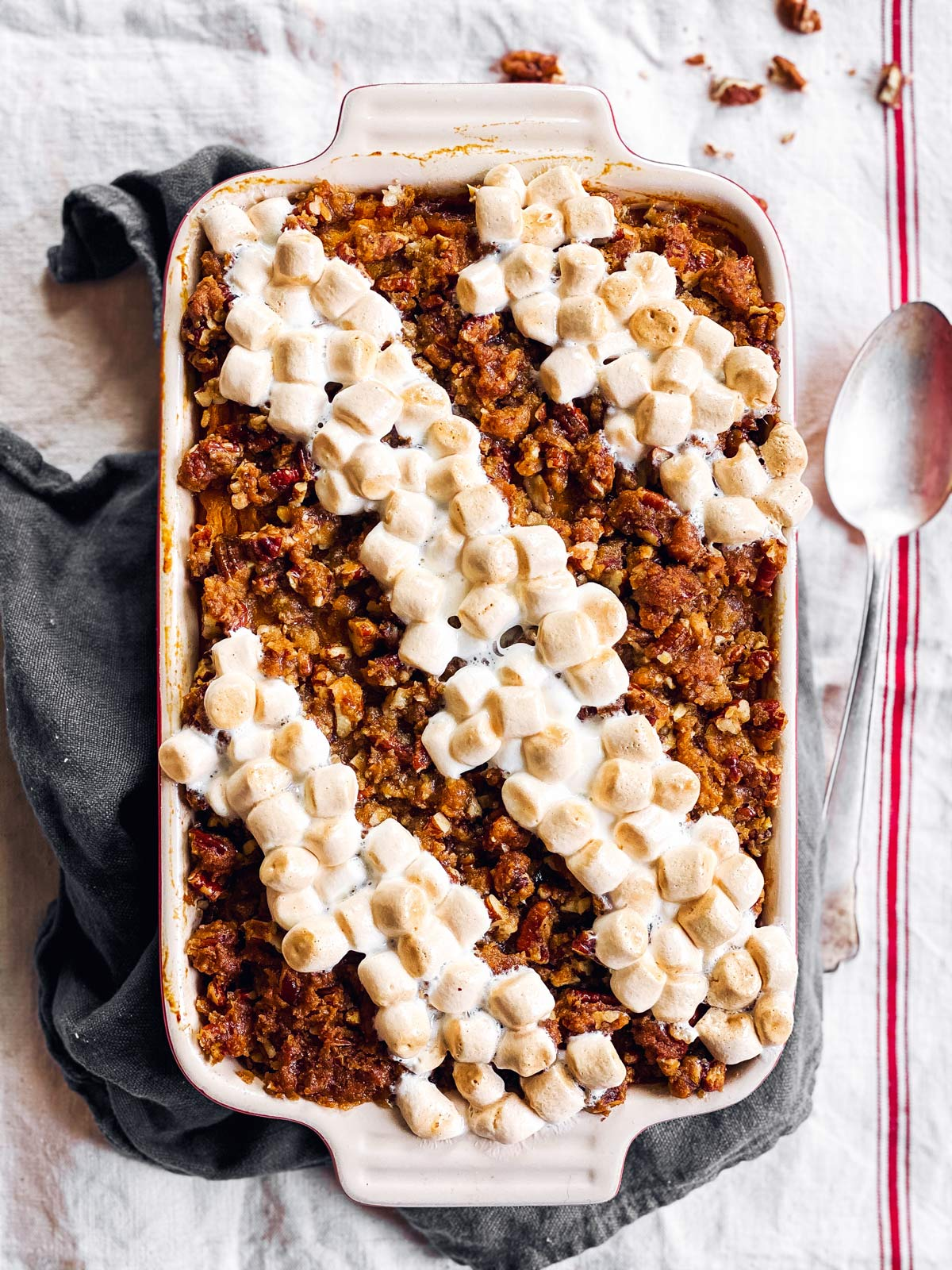 sweet potato casserole with marshmallows and pecan praline topping on a table cloth