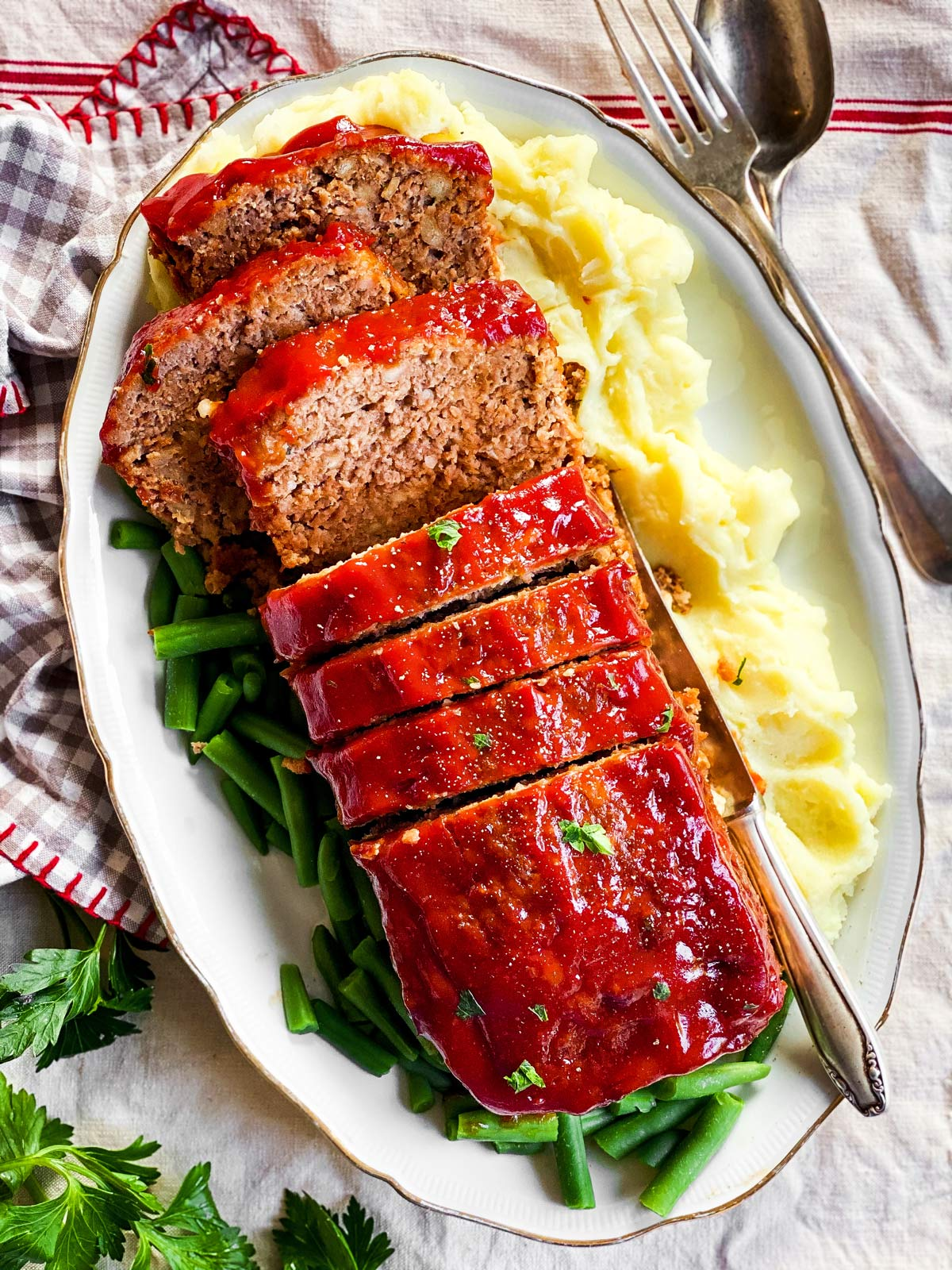 sliced meatloaf on a platter with mashed potatoes and green beans