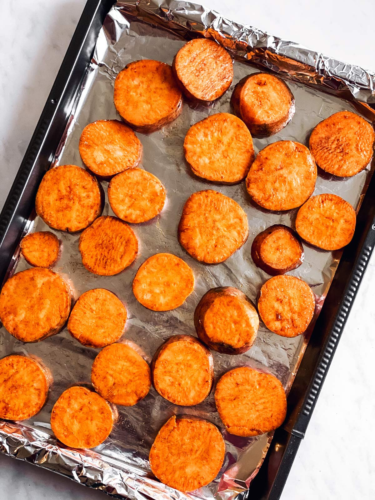 baking sheet with raw sweet potato slices