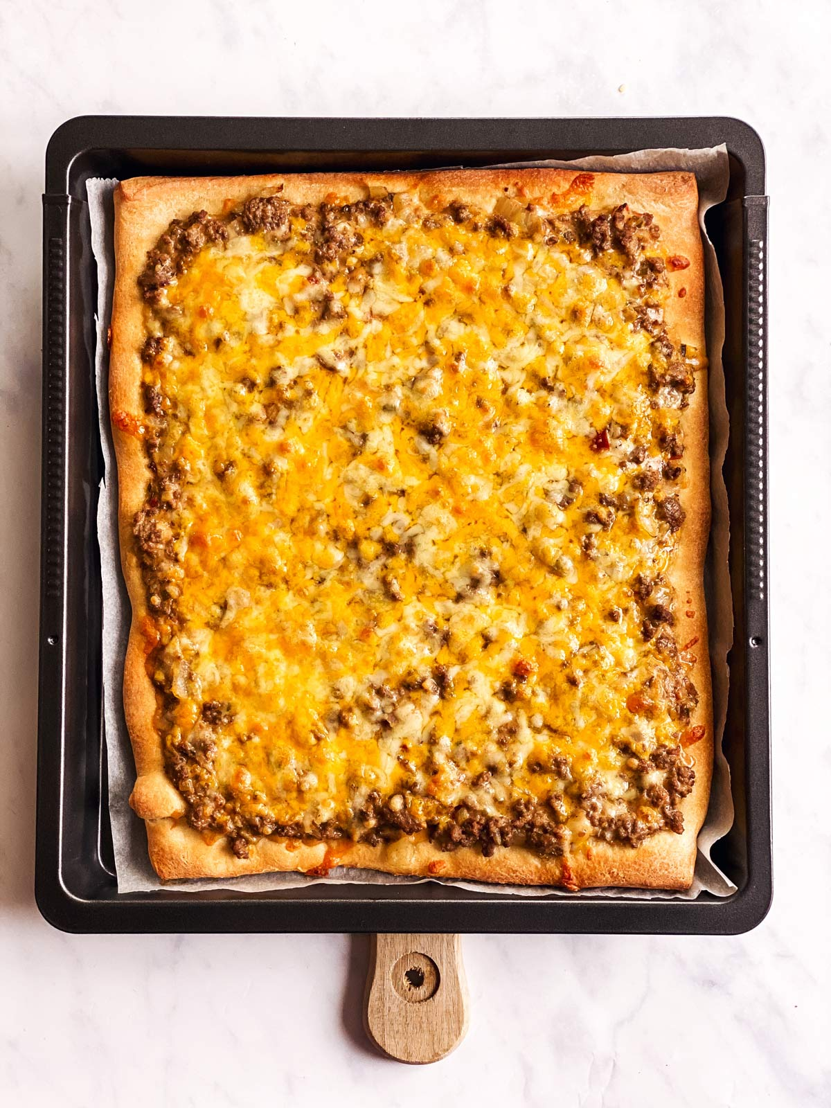 baked Big Mac pizza on dark baking pan