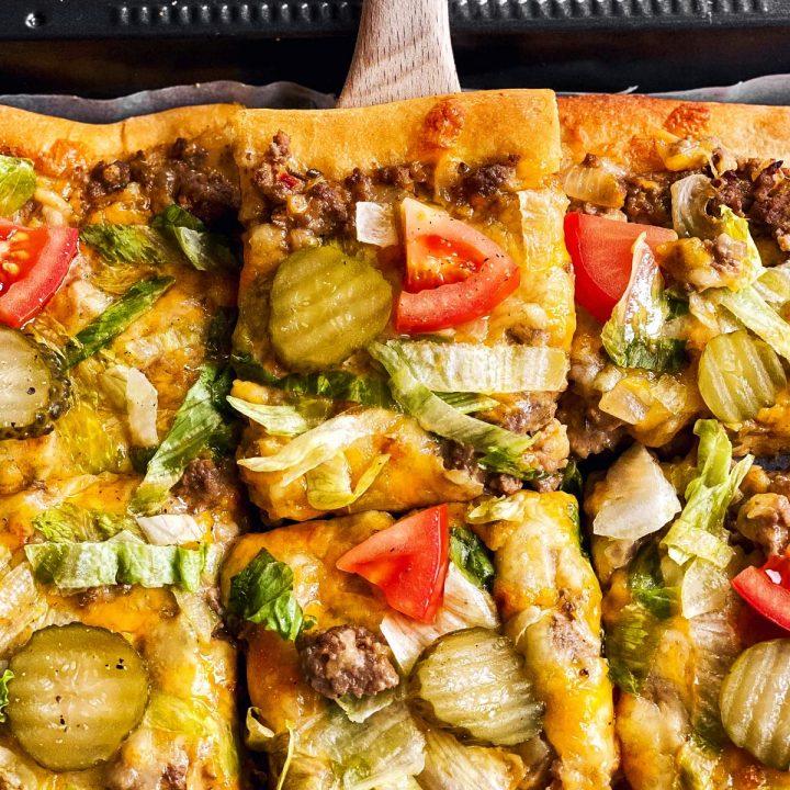 close up photo of wooden spatula lifting slice of Big Mac pizza from pan