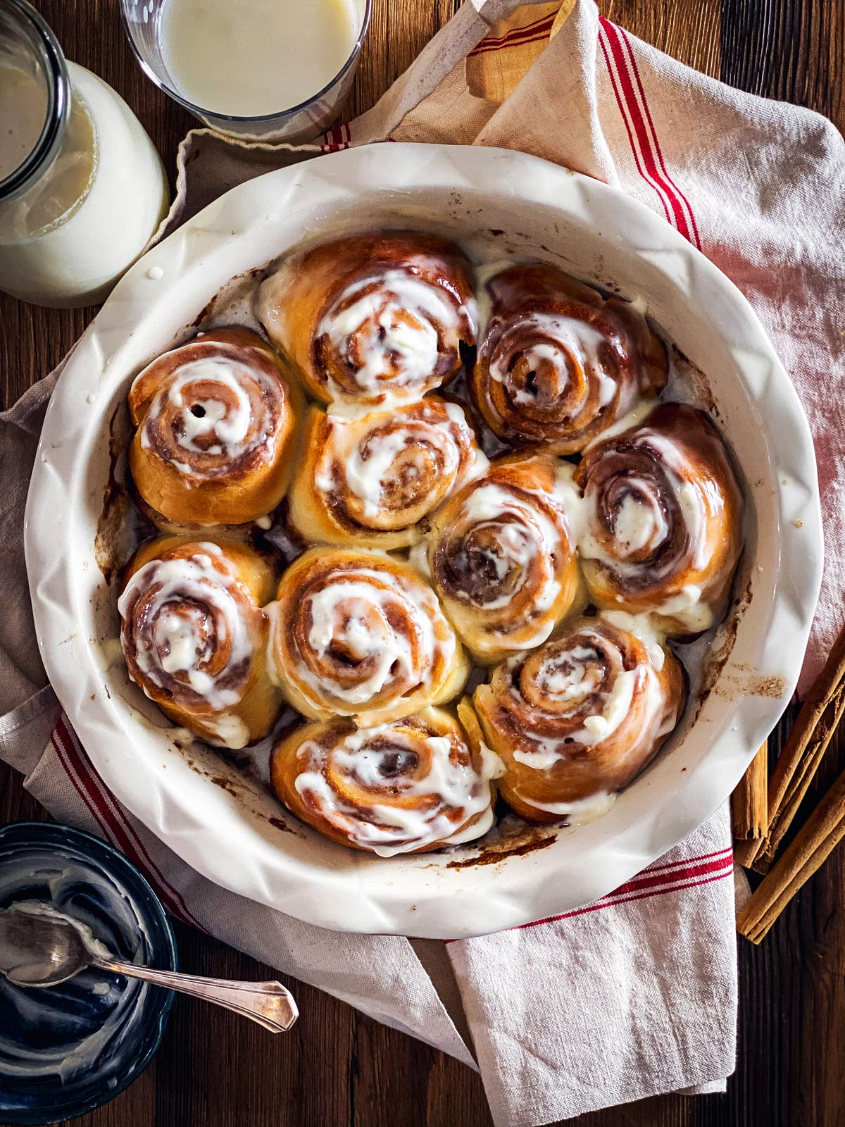 round pan with baked cinnamon rolls on wooden surface